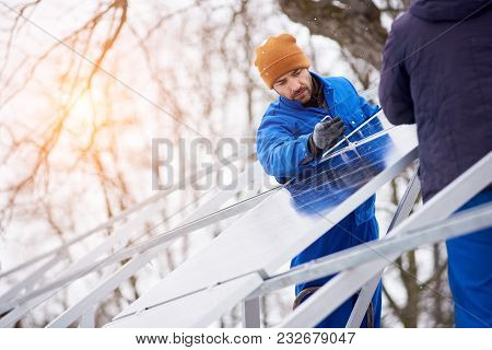 Technicians In Blue Suits Installing Photovoltaic Solar Modules On Roof Of Modern House. Solar Panel