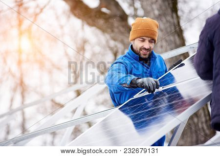Handsome Bearded Mature Male Electrician Worker Smiling While Installing Solar Pannels On Power Plan