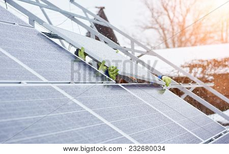 Group Of Professionals Installing Photovoltaic Solar Panels On The Roof Of Modern House During Snowy