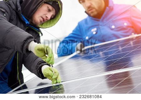 Technicians In Blue Suits Mounting Photovoltaic Solar Panels On Roof Of Modern Houses. Solar Modules