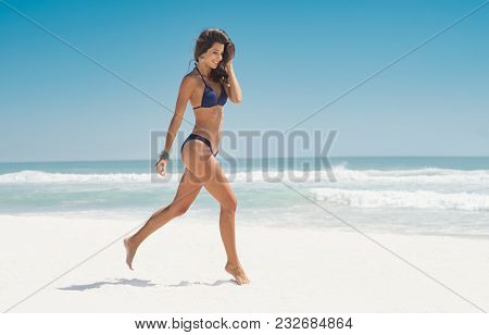 Happy smiling woman jumping on the beach. Beautiful young woman running on tropical beach. Happy latin girl walking on white sand beach during summer vacation with copy space.