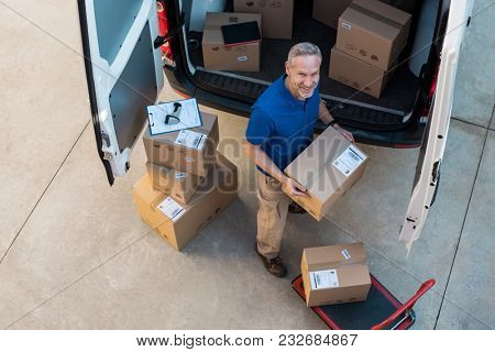 Happy delivery man holding cardboard package and looking at camera. Top view of courier loading packages in van for delivery. Portrait of man working at courier service and carrying parcels on van.