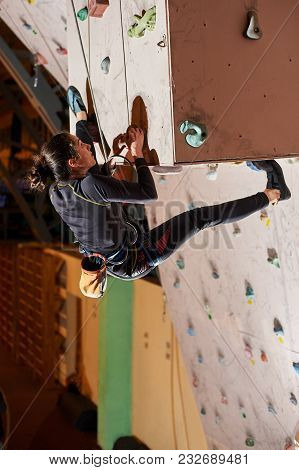 Young Woman Climbing Up On Practice Wall In Gym Indoors. The Concept Of Sport And Health At Any Time