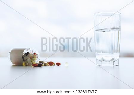 Close up of blurry white workplace with pills and tablets. Medicine and dose concept poster