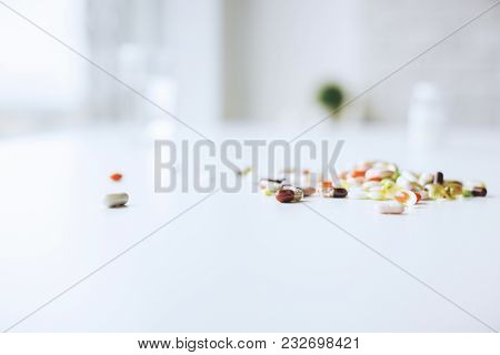 Close up of blurry white desktop with pills and tablets. Medicine and dose concept poster