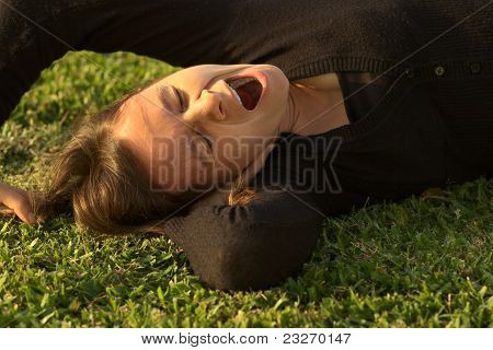 Young Woman Yawning on Grass