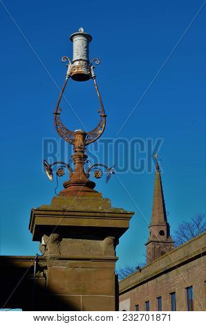 An Old Stone And Metalwork Gatepost With A Church Spire In The Distance