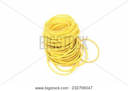 Pile of yellow rubber bands isolated on white background. Packaging supplies and accessory. Thin rub