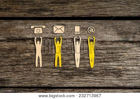 Teamwork And Customer Service Concept With Cut Outs Of Four Men Supporting A Line Of Phone, Web And