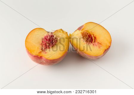 Fresh dissected peach with stone on white background poster