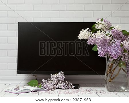 Beautiful White And Violet Lilac Flowers Bouquet In Glass Vase With Opened Note-book And Black Monit
