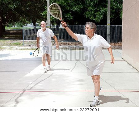 Active senior couple playing racquetball on a public court.