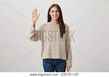 Girl Waves Her Friend So She Can Find Her In Crowd. Studio Shot Of Positive Charming Woman In Casual