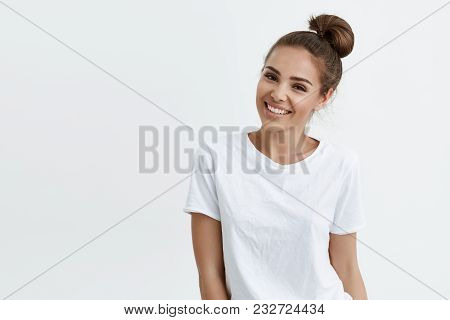 Positive Slim European Girl With Bun Hairstyle, Smiling Broadly While Standing Over White Background