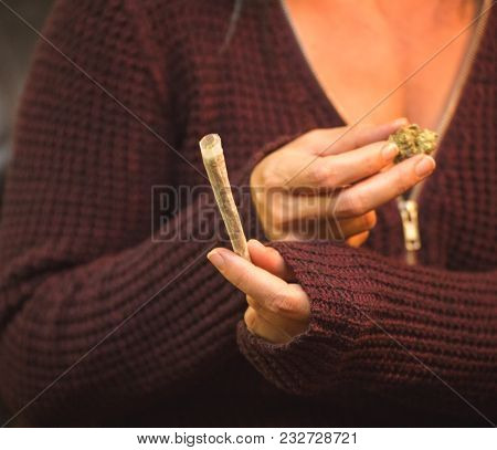 Woman Holding A Cannabis Bud In One Hand And A Joint In The Other.