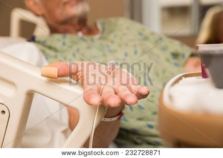 Elderly Caucasian Man Wearing Oxygen Tube While Resting In A Hospital Bed.