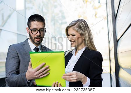 Two Young Business People Analyze The Results And Discuss
