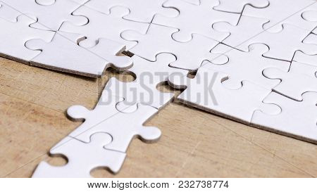 White Jigsaw/puzzle With A Row In Wrong Position, Over  Wooden Table Background, Symbol Of Problem S