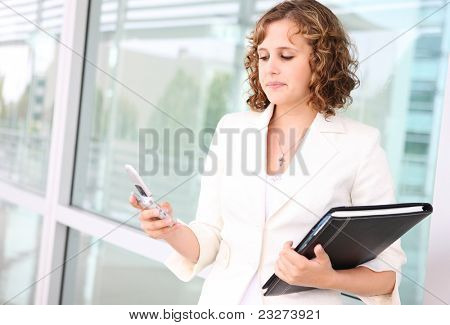 A pretty caucasian woman texting at her office building looking sad