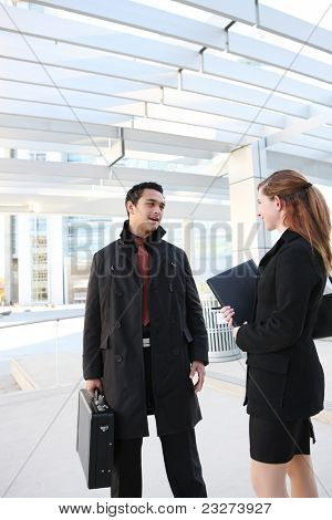 A Hispanic Man and Caucasian Business Woman at their company building