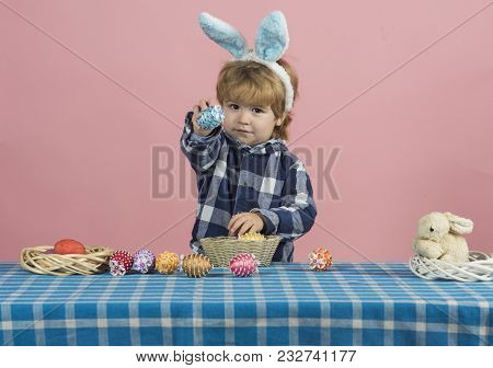 Easter Egg, Cute Blond Boy With Brown Eyes Shows Toy Egg From Bowl. Table Decorated With Blue And Wh