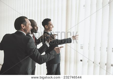 Three Joyful Friends Looking Out The Window With Jalousie And Pointing. Copy Space In Right Side