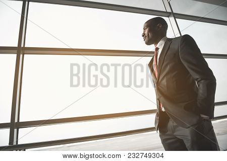 Low Angle Of Peaceful African Businessman Looking Through Large Window. Copy Space In Left Side