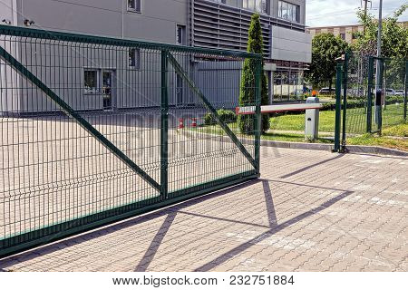 Green Metal Gate And Barrier On The Sidewalk In Front Of The Industrial Building