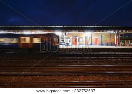 Commuter Train Departing A Uk Station At Night