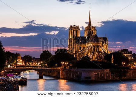 View Of Southern Facade Of Notre Dame De Paris From The Seine River At Night. Notre Dame Cathedral