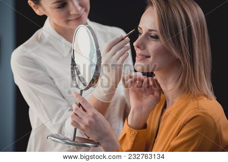 Smiling Visagiste Painting Brows Of Glad Young Woman. She Watching At Reflection. Glad Professional
