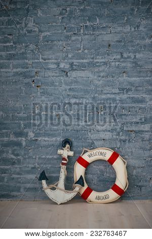 A Composition On A Sea Theme With An Anchor And Life Ring On A Gray Brick Wall
