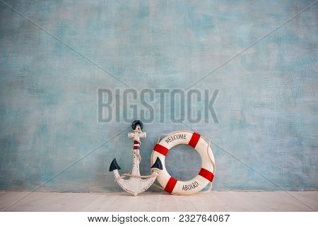 A Composition On A Sea Theme With An Anchor And Lifebuoy On A Blue Wall.