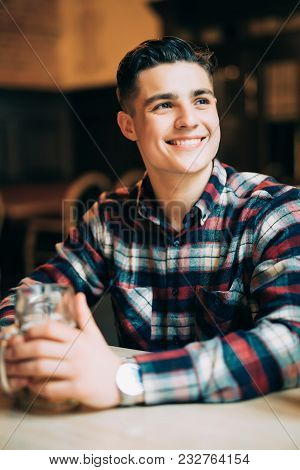 Young Man Sitting At Pub Table With A Pint Of Light Beer
