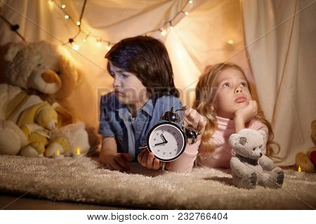 Kids Holding In Hand Clock. Alarm Indicates Late Time. They Are Felling Chagrin. Boy And Girl In Bea