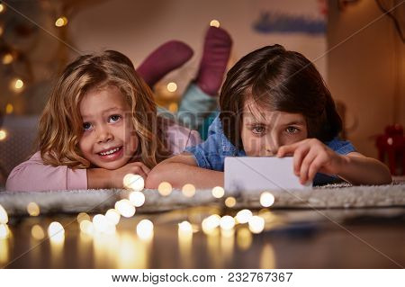 Focus On Smiling Enthusiastic Kids Using Modern Smartphone. They Are Lying On Carpet In Cozy Childre