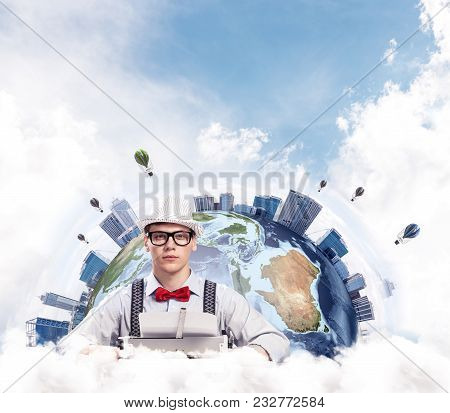 Young Man Writer In Hat And Eyeglasses Using Typing Machine While Sitting At The Table With Earth Gl
