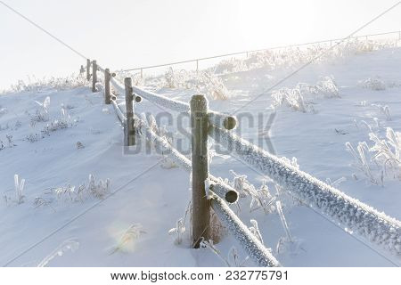 Horizontal Close Up Image Of A Snow  And Frost Covered Wooden  Fence  Poles Running Over A Hill With