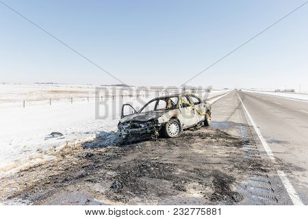Horizonta Full Length Image Of A Badly Burned Out Car  With Yellow Caution Tape Around It Sitting On