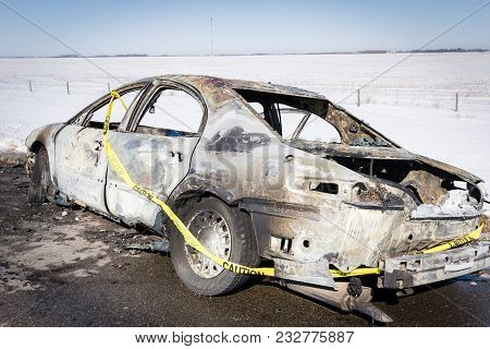 Horizontal Image Of A Completely Burned Out Car Surrounded By Yellow Police Tape On The Side Of The