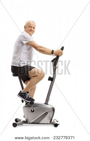 Mature man on a stationary bike looking at the camera isolated on white background