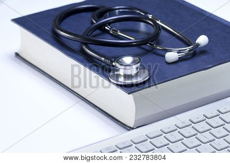 Medical Student Textbook With Black Stethoscope And Modern White Computer Keyboard Isolated On White