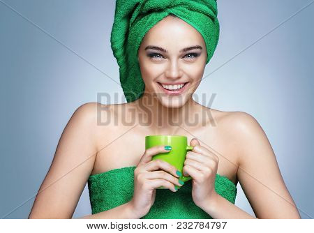 Good Morning! Attractive Girl In Green Towels With Cup Of Tea On Blue Background.