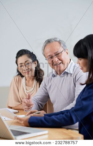 Pretty Asian Estate Agent Showing Where To Put Signature After Reached Agreement With Loving Senior
