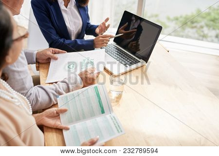 Senior Couple Studying Terms Of Life Insurance Policy While Having Meeting With Highly Professional
