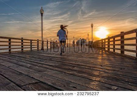 A Girl Running On Oceanside Pier At Sunset, California