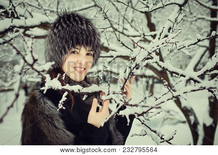 Portrait Of Beautiful Young Girl In Fur Coat And Fur Hat Smiling And Spending Time Outdoors In The W