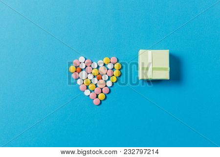 Medication White, Colorful Round Tablets In Form Of Heart Isolated On Blue Background. Square Shape