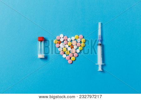 Medication White, Colorful Round Tablets In Form Of Heart Isolated On Blue Background. Pills, Bottle
