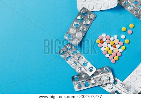 Medication Colorful Round Tablets In Form Of Diffusion Heart Isolated On Blue Background. Empty Pack